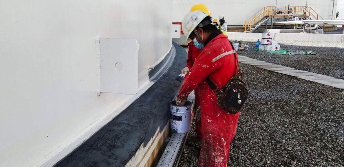 Technician applying belzona 3921 to tank base