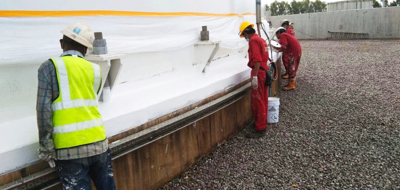 Four technicians apply final coat of Belzona 3111 to the tank base