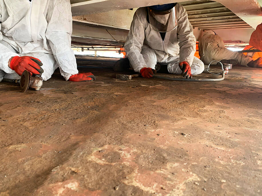 Two workers conducting surface preparation on Roof repair